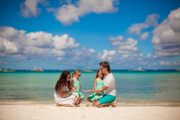Giovane bella famiglia con due figlie divertirsi in spiaggia Foto Premium