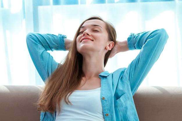 Giovane, bella, felice donna rilassante che riposa sul divano di casa dopo una lunga giornata di lavoro e godendo la solitudine Foto Premium