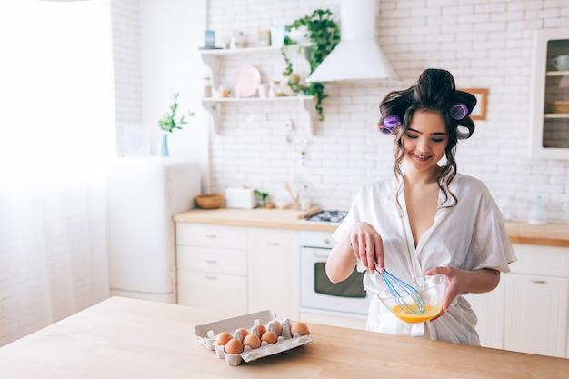 Giovane bella governante femminile che cucina nella cucina. frullare le uova in una ciotola di vetro. guarda in basso e sorridi. bigodini nei capelli. solo in cucina. daylight. indossa una vestaglia bianca. Foto Premium