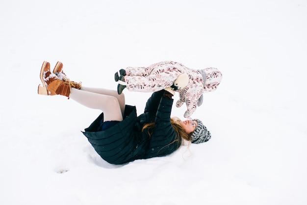 Giovane bella madre che gioca con la piccola figlia all'aperto in inverno. la femmina sorridente allegra felice con il bambino adorabile si diverte in neve. Foto Premium