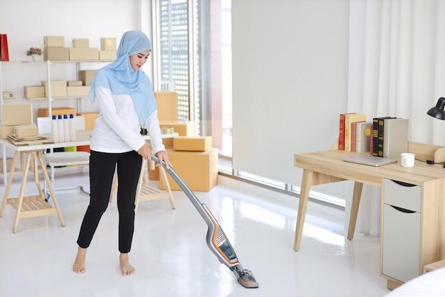Giovane bella pulizia musulmana asiatica attiva della donna della casalinga con il pavimento di pulizia di vuoto Foto Premium