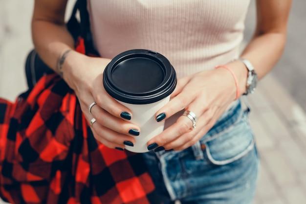 Giovane bella ragazza beve il caffè in un bicchiere per strada, ride e sorride Foto Gratuite