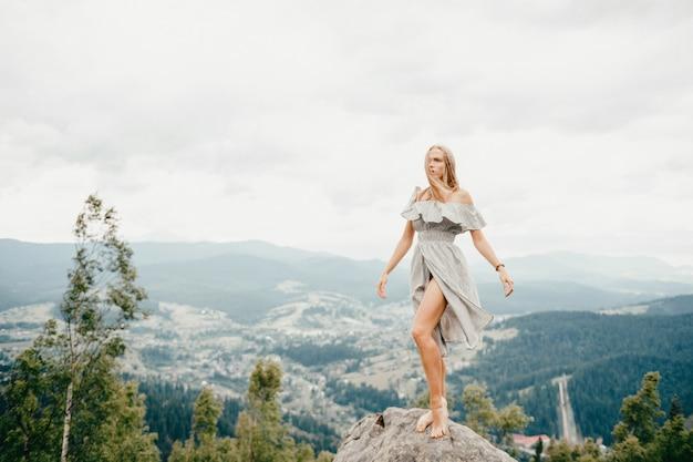 Giovane bella ragazza bionda scalza con capelli lunghi in vestito da estate che sta sopra la montagna alla pietra e che gode della vista scenica del paesaggio favoloso. Foto Premium