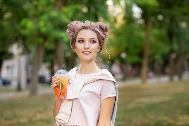 Giovane bella ragazza che beve succo fresco dalle tazze di plastica asportabili dell'alimento dopo una passeggiata all'aperto. uno stile di vita sano. bionda esile sorridente con capelli rosa. Foto Premium