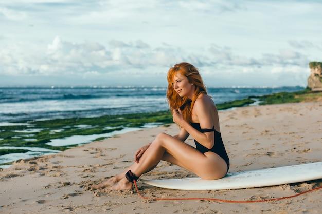 Giovane bella ragazza in posa sulla spiaggia con una tavola da surf, donna surfista, onde dell'oceano Foto Gratuite