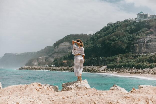 Giovane bella ragazza in posa sulla spiaggia, oceano, onde, sole splendente e pelle abbronzata Foto Gratuite
