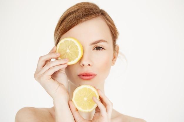 Giovane bella ragazza nuda con l'occhio nascondentesi della pelle sana pulita dietro la fetta del limone. cosmetologia di bellezza spa. Foto Gratuite