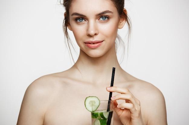 Giovane bella ragazza nuda con pelle pulita perfetta che sorride esaminando macchina fotografica che tiene bicchiere d'acqua con le fette del cetriolo sopra fondo bianco. trattamento facciale. Foto Gratuite