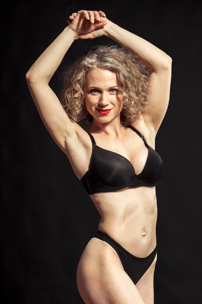 Giovane bella ragazza nuda isolata su una priorità bassa nera Foto Premium