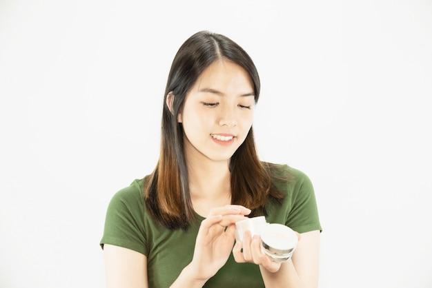 Giovane bella signora con crema idratante per la cura della pelle del viso - donna e cosmetici trucco viso bellezza concetto di cura della pelle Foto Gratuite