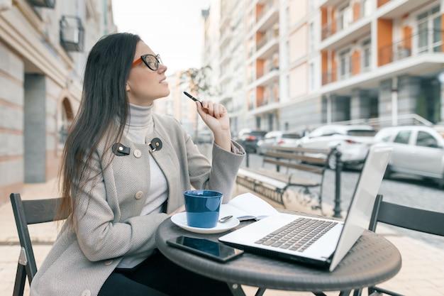Giovane bella studentessa che si siede in caffè all'aperto con il computer portatile Foto Premium
