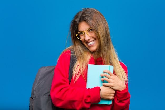 Giovane bella studentessa sentirsi romantica, felice e innamorata, sorridendo allegramente e tenendosi per mano vicino al cuore Foto Premium
