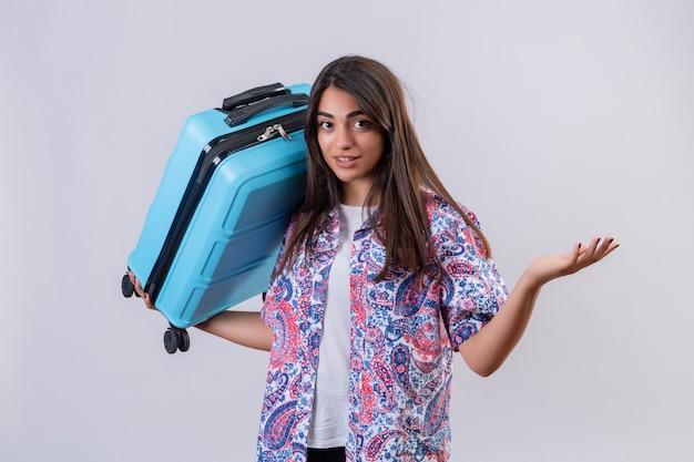 Giovane bella valigia della tenuta della donna del viaggiatore che sembra gesturing confuso con la mano e l'espressione come fare una domanda sopra la parete bianca Foto Gratuite