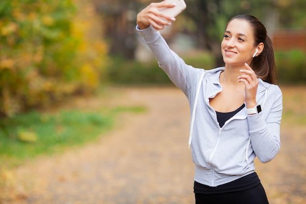 Giovane bellezza con lunghi capelli castani guardando smartphone prendendo foto di se stessa Foto Premium