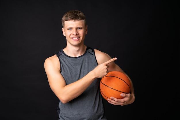 Giovane bello che gioca pallacanestro sopra la parete nera isolata Foto Premium