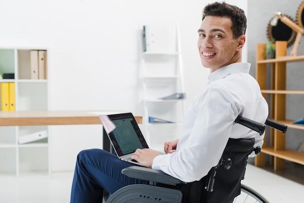 Giovane bello che si siede sulla sedia a rotelle con il computer portatile che guarda l'obbiettivo Foto Gratuite
