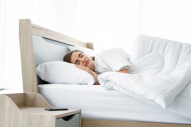 Giovane bello dormire nel letto di casa. Foto Premium