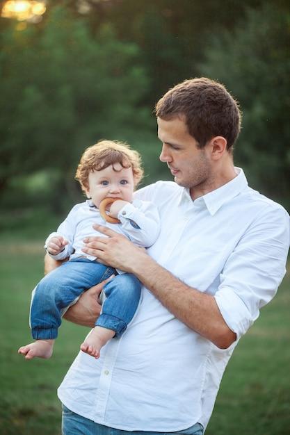 Giovane bello padre e piccolo figlio del bambino contro erba verde Foto Gratuite
