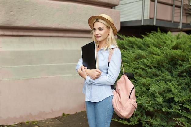 Giovane bionda studente in un cappello di paglia e una parte anteriore zaino rosa dell'università Foto Premium