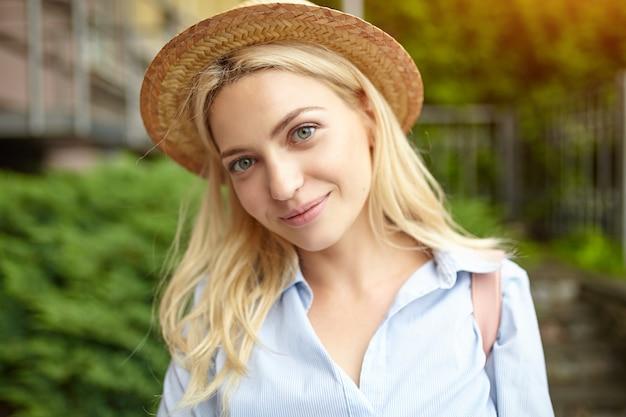 Giovane bionda studente in un cappello di paglia in piedi sulla parte anteriore dell'università. Foto Premium