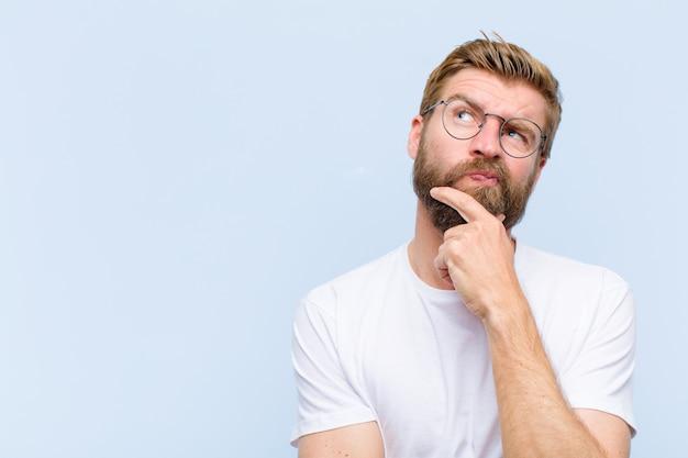 Giovane biondo adulto che pensa, si sente dubbioso e confuso, con diverse opzioni, chiedendosi quale decisione prendere Foto Premium