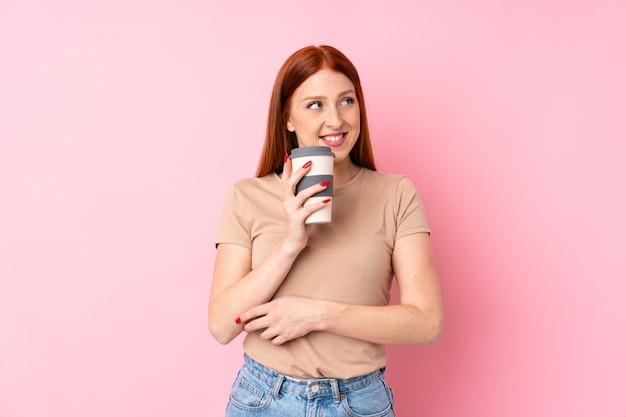 Giovane caffè della tenuta della donna della testarossa da portare via Foto Premium