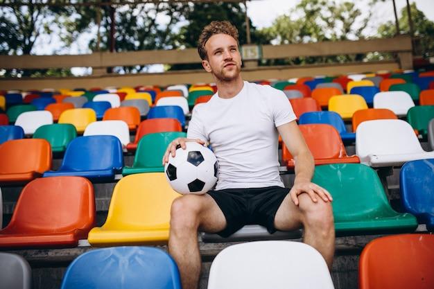 Giovane calciatore alle tribune che guardano la partita Foto Gratuite