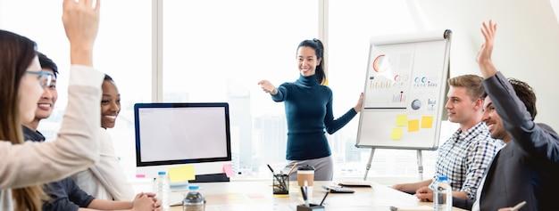 Giovane capo asiatico della donna di affari che chiede l'opinione nella riunione Foto Premium