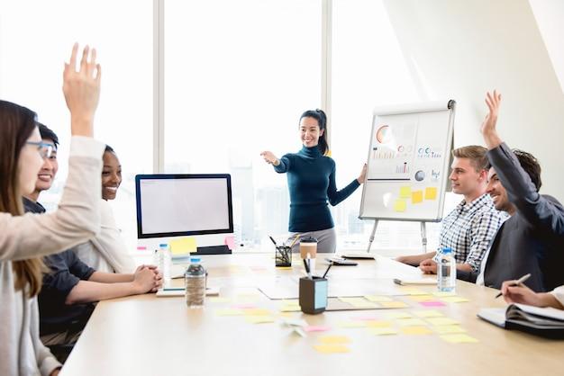 Giovane capo casuale della donna di affari asiatica che chiede l'opinione nella riunione Foto Premium