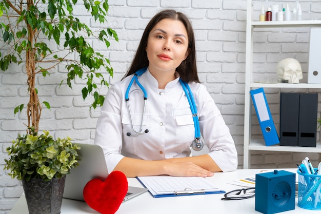 Giovane cardiologo medico femmina seduto alla sua scrivania e il suo lavoro Foto Premium