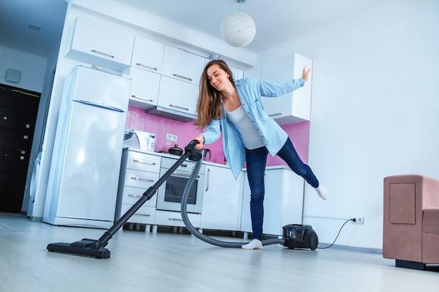 Giovane casa di pulizia felice della persona di pulizia facendo uso dell'aspirapolvere. faccende domestiche e servizio di pulizia. concetto pulito Foto Premium