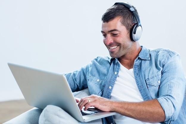 Giovane che ascolta la musica mentre per mezzo del computer portatile Foto Premium