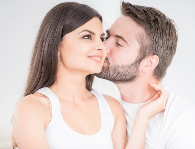 Giovane che bacia teneramente la sua donna sulla guancia. Foto Premium