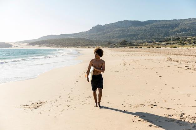 Giovane che cammina lungo la spiaggia che trasportano surf Foto Gratuite