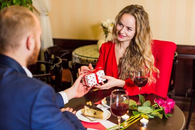 Giovane che dà il contenitore di regalo alla donna alla tavola in ristorante Foto Gratuite