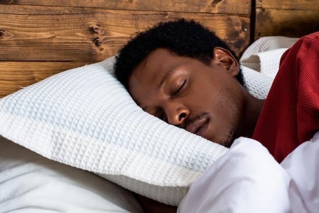Giovane che dorme nel letto Foto Premium