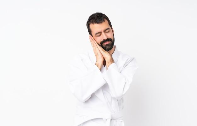 Giovane che fa karatè sopra fondo bianco isolato che fa gesto di sonno nell'espressione dorable Foto Premium