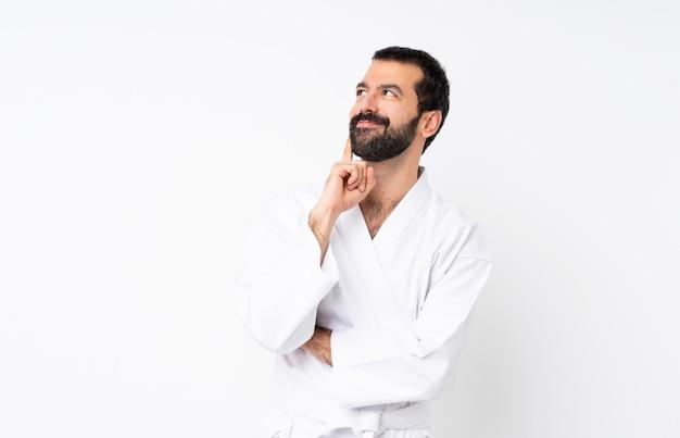 Giovane che fa karatè sopra la parete bianca isolata che pensa un'idea mentre osservando in su Foto Premium