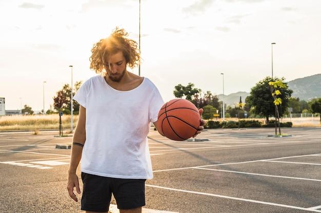 Giovane che gioca a pallacanestro in tribunale Foto Gratuite