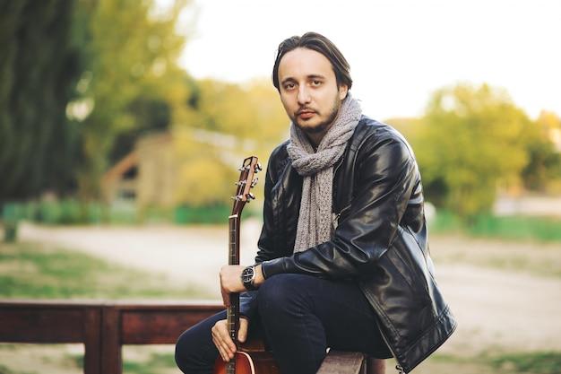 Giovane che gioca alla chitarra nel lago Foto Gratuite