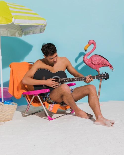 Giovane che gioca chitarra sulla spiaggia Foto Gratuite