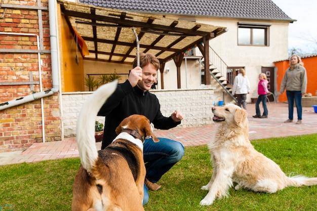 Giovane che gioca con i suoi cani in giardino Foto Premium