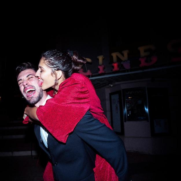 Giovane che grida uomo che tiene indietro donna attraente felice sulla strada Foto Gratuite