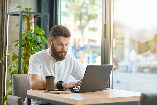 Giovane che lavora con il computer portatile che si siede vicino a finestre panoramiche. Foto Premium