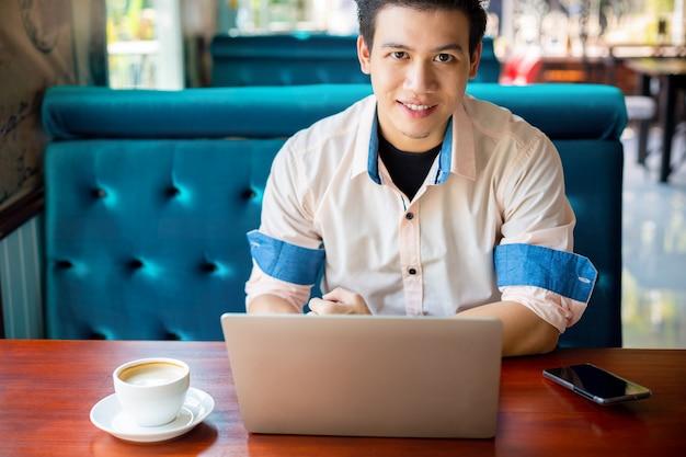 Giovane che lavora con il computer portatile in caffè Foto Gratuite