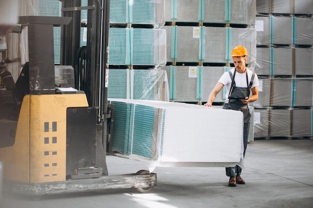 Giovane che lavora in un magazzino con scatole Foto Gratuite