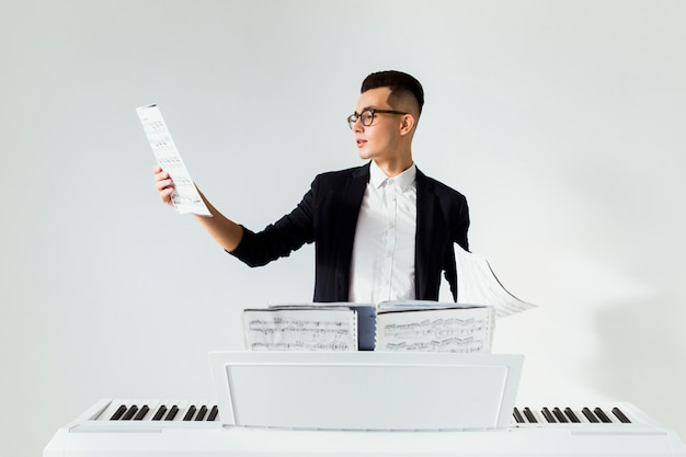 Giovane che legge lo strato musicale che sta dietro il piano contro fondo bianco Foto Gratuite
