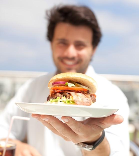 Giovane che mangia un hamburguer Foto Premium