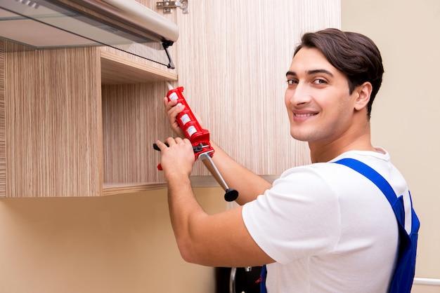 Giovane che monta i mobili della cucina Foto Premium