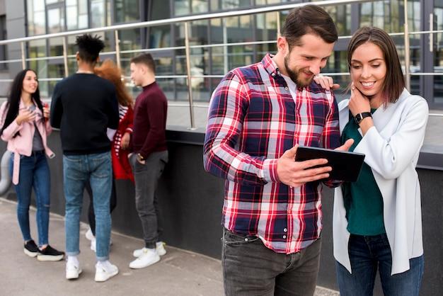 Giovane che mostra compressa digitale al suo amico in piedi vicino alla folla Foto Gratuite